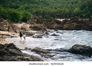 beautiful young couple in love holding their hands and walking on the beach, looking at the sea. big rocks  stones background.  landscape. Concept of honeymoon