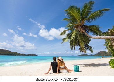 Beautiful young couple in love sitting and relaxing on exotic beach surrounded by palm tree and blue sea from Seychelles Islands. Young couple in honeymoon having holidays on exotic beach