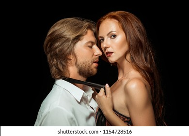 Beautiful young couple in love standing together against black studio background. Passion, sensuality, youth, feeling, erotic, sex, kiss, relationship concept