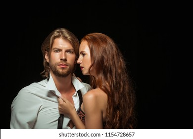 Beautiful young couple in love standing together against black studio background. Passion, sensuality, youth, feeling, erotic, sex, relationship concept