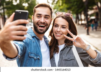 Beautiful young couple in love standing outdoors at the city street, taking a selfie, showing peace gesture