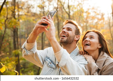 Beautiful young couple in love using mobile phone while spending time at the autumn park, taking a selfie
