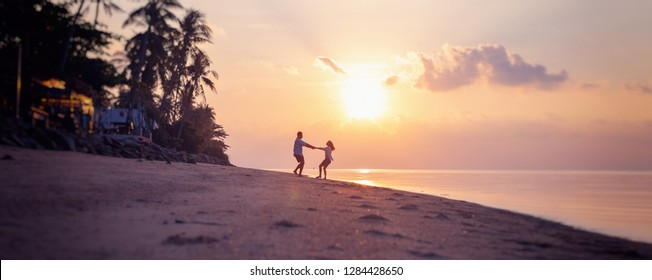 Beautiful young couple in love whirls holding hands on the beach at sunset during the honeymoon vacation travel Valentines day