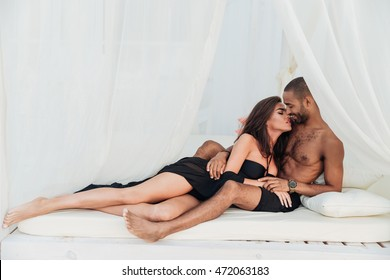 Beautiful young couple lying and kissing on white bed