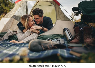Beautiful young couple lying in a tent. Happy loving couple resting in tent on campsite.