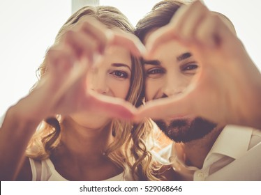 Beautiful young couple is making heart of fingers and smiling while celebrating at home
