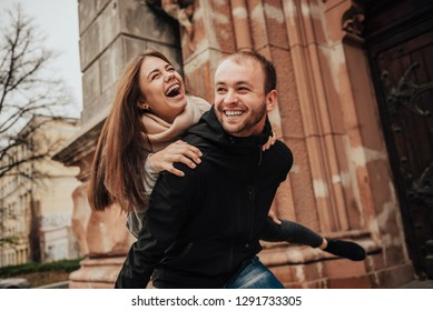 Beautiful young couple. Man piggybacking his girlfriend on the streets