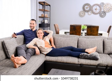 beautiful young couple man and woman at home relaxed on sofa and watching tv
