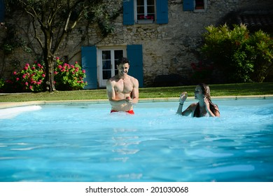 beautiful young couple man and woman on summer holiday in swimming pool resort