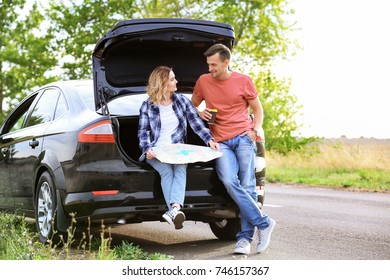 Beautiful young couple with map near car