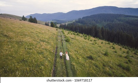 Beautiful young couple in the mountains. Photo from the drone. Wedding walk in the mountains.