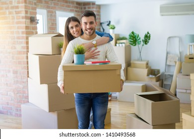 Beautiful young couple moving to a new house, smiling happy holding cardboard boxes at new apartment