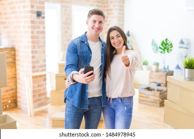 Beautiful young couple moving to a new house using smartphone happy with big smile doing ok sign, thumb up with fingers, excellent sign