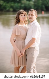 beautiful young couple near a large river, cuddling, standing watching with a smile, pressed against each other, in nature. summer, walk