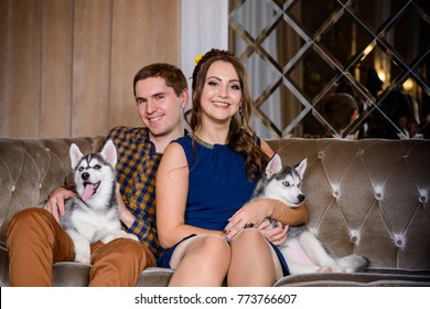 Beautiful young couple in the New Year atmosphere with puppies of the Husky