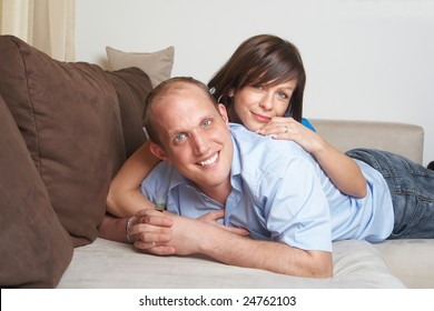 Beautiful young couple on a couch in their new appartment.