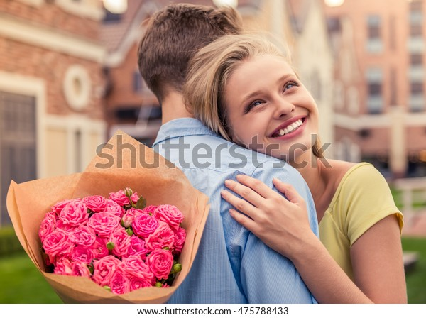 Beautiful young couple on a date. Attractive girl is hugging her boyfriend, holding flowers and smiling