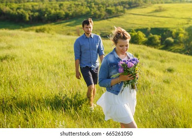 Beautiful young couple in park. Girl with flowers in front