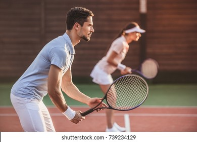 Beautiful young couple are playing tennis as a team on tennis court outdoors