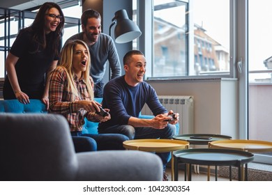 Beautiful young couple playing video games with friends in the living room