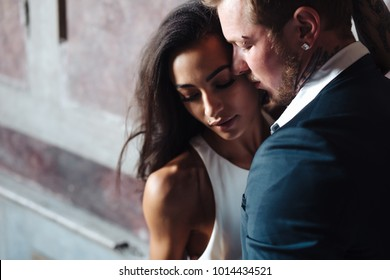 Beautiful, young couple posing on camera indoors. Beautiful model girl in white dress. Man in suit. Cute lady and handsome guy