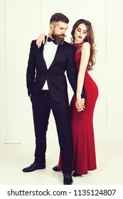 Beautiful, young couple posing on camera. Beautiful model girl in red dress. Man in black suit. Cute lady and handsome guy. Fashion, beauty, style concept. Bearded man. Couple in love. Gravity of love