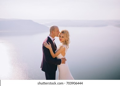 beautiful young couple posing on the rock near the lake