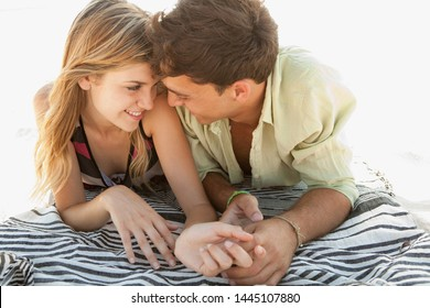 Beautiful young couple relaxing on beach summer holiday, holding hands smiling together, sunny vacation tourists outdoors. Travel holiday coastal leisure recreation lifestyle, honeymoon romance.