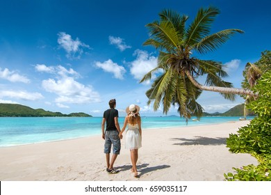 Beautiful young couple relaxing on an exotic beach from Seychelles. Couple in love travel on honeymoon on exotic island. Young lovers under palm tree and surrounded by blue sea from Seychelles Islands