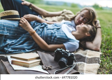 beautiful young couple relaxing in park on plaid