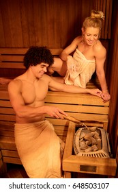 Beautiful young couple relaxing in a sauna at the spa centre.