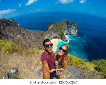 Beautiful young couple selfie on the cliff in Kelingking beach in Nusa Penida, Indonesia on a sunny day with blue sky and crystal clear water