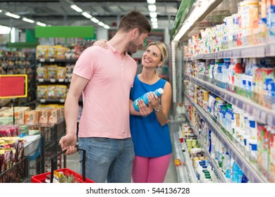 Beautiful Young Couple Shopping For Milk And Cheese In Produce Department Of A Grocery Store - Supermarket - Shallow Deep Of Field