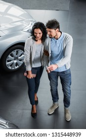 Beautiful young couple in the showroom, choosing a car. Top view.