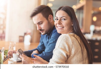Beautiful young couple sitting in a cafe, drinking coffee and having fun with tablet. Students during break in the cafe. Love, romance, dating, lifestyle