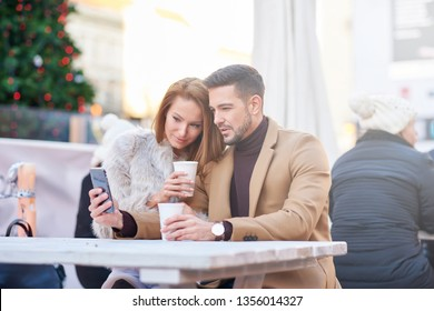 A beautiful young couple sitting and drinking mulled wine while taking a selfie with a christmas tree in the background.