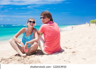 beautiful young couple sitting and having fun on beach