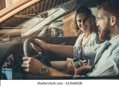 Beautiful young couple is sitting in a new car in car dealership