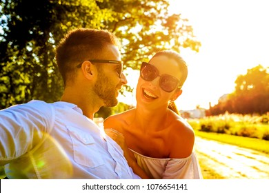 A beautiful young couple sitting on a bench in a park in the sunset