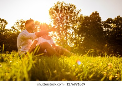 A beautiful young couple sitting on a field in a park in the sunset