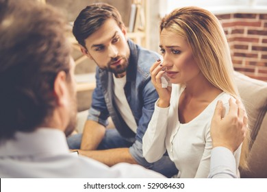 Beautiful young couple is sitting on couch and talking to the psychologist. Woman is crying