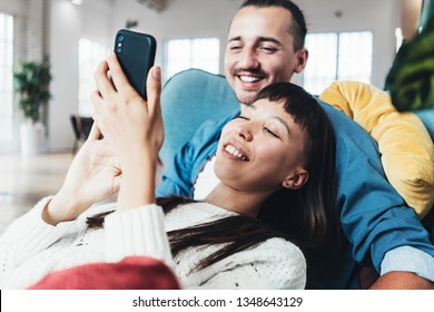 Beautiful young couple sitting together and hugging in big loft apartment and using mobile phone