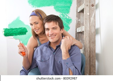 Beautiful young couple sitting together with color roller at home