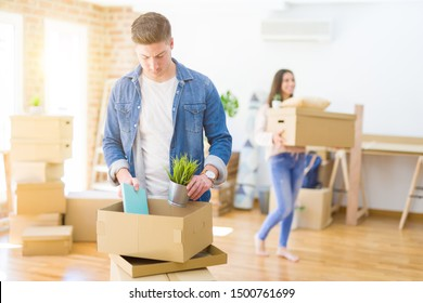 Beautiful young couple smiling in love holding cardboard boxes,