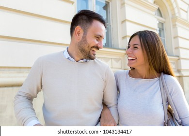 Beautiful young couple smiling while walking outdoors on sunny day