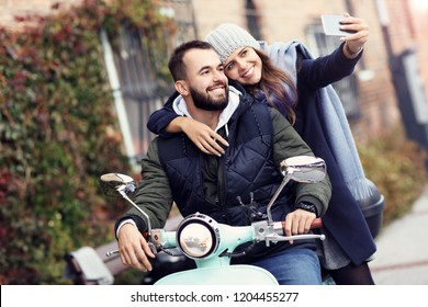 Beautiful young couple smiling while riding scooter in city in autumn