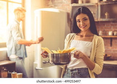 Beautiful young couple is smiling while cooking in kitchen at home. Woman is holding a pan with spaghetti and looking at camera