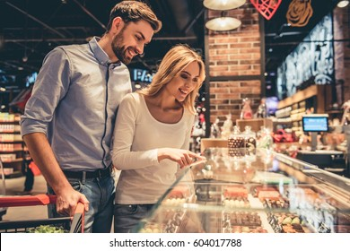 Beautiful young couple is smiling while doing shopping at the supermarket