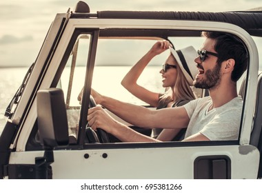 Beautiful young couple is smiling while travelling by car in sunny weather