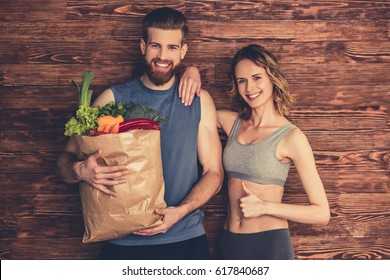 Beautiful young couple in sportswear is holding a shopping bag full of healthy food,looking at camera and smiling, on wooden background